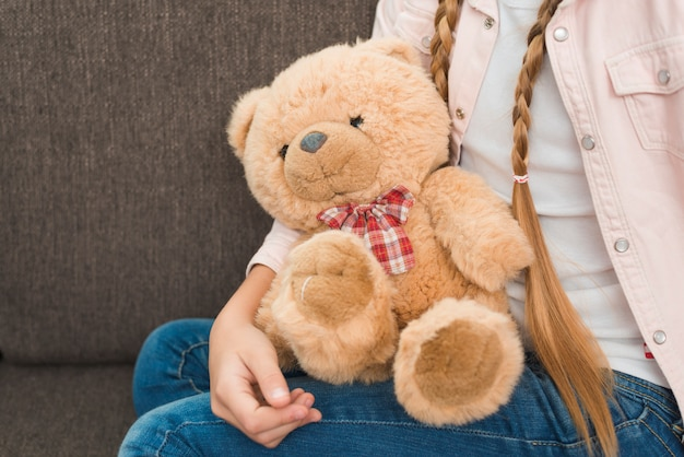 Primer plano de una niña sentada en el sofá con suaves osos de peluche