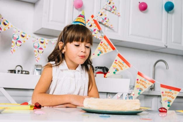 Primer plano de una niña con sombrero de fiesta en la cabeza soplando velas en el pastel