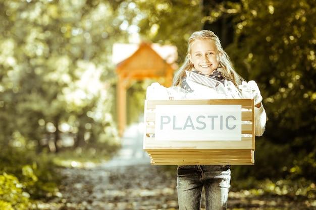 Un primer plano de una niña sonriente con basura de plástico en las manos en el bosque en un buen día