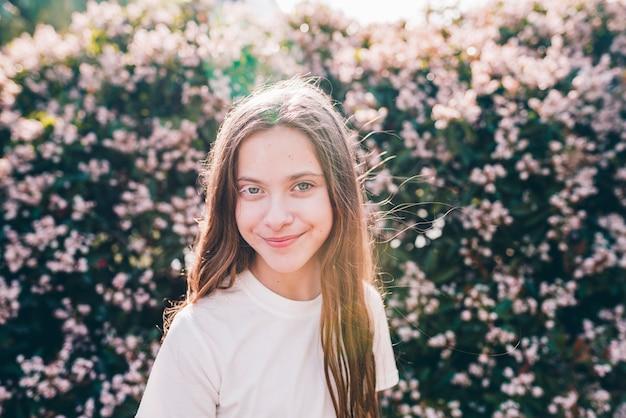 Primer plano de una niña sonriente bonita de pie contra las plantas de flor