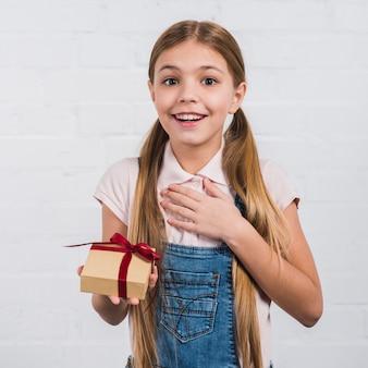 Primer plano de una niña sonriente complacida con una caja de regalo envuelta contra una pared blanca