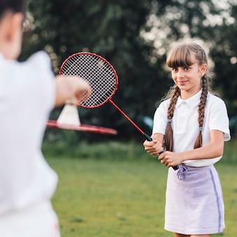 Primer plano de una niña sonriente jugando bádminton con su amiga