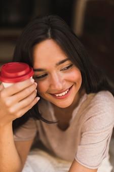 Primer plano de una niña sonriente sosteniendo una taza de café para llevar
