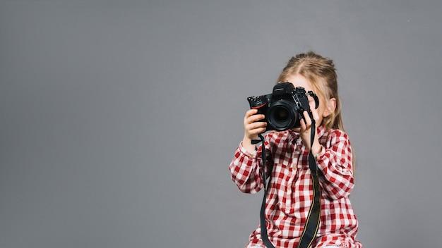 Primer plano de una niña sosteniendo una cámara frente a su cara de pie contra el fondo gris