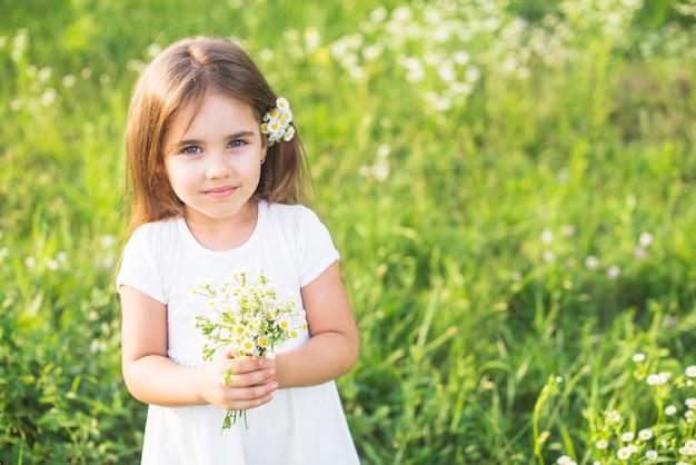 Primer plano de niña sosteniendo ramo de flores blancas en el prado