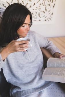 Primer plano de una niña sosteniendo una taza de café leyendo el libro