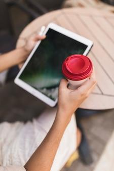 Primer plano de una niña con tableta digital y taza de café desechable