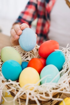 Primer plano de una niña tomando huevo de pascua azul del nido