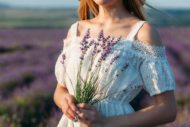 Primer plano de una niña en un vestido blanco con un ramo de lavanda en sus manos