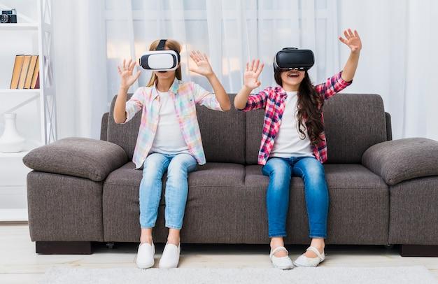 Primer plano de las niñas sentadas en el sofá tocándose en el aire durante la experiencia vr