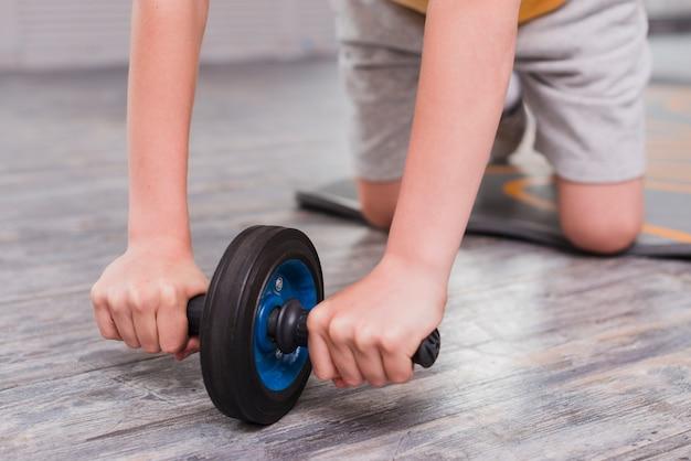 Primer plano de un niño arrodillado ejercicio con rodillo deslizante