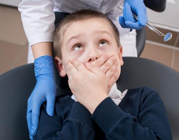Primer plano de un niño asustado por los dentistas cubre su boca y lo busca