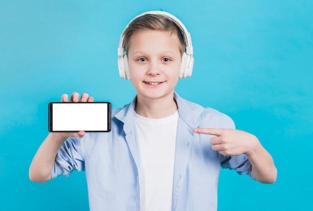 Primer plano de un niño con auriculares en la cabeza apuntando su dedo hacia el teléfono móvil con pantalla en blanco