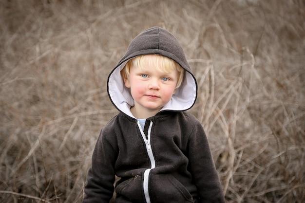 Primer plano de un niño caucásico blanco con cabello rubio con una chaqueta negra