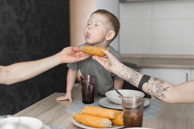 Primer plano de un niño comiendo maíz sostenido por su padre en el desayuno