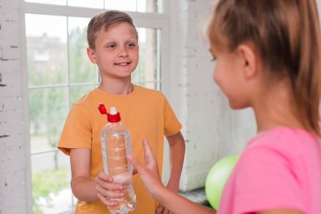 Primer plano de un niño dando botella de agua a su amigo
