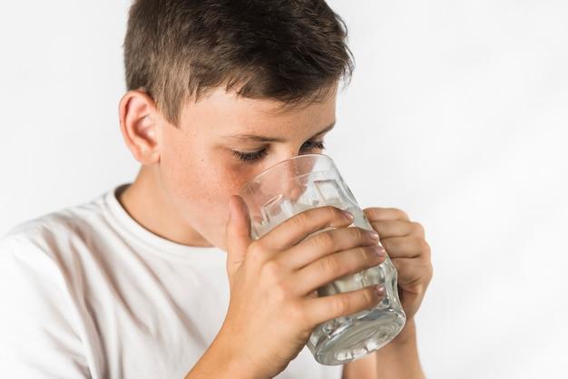Primer plano de un niño con leche en vaso sobre fondo blanco