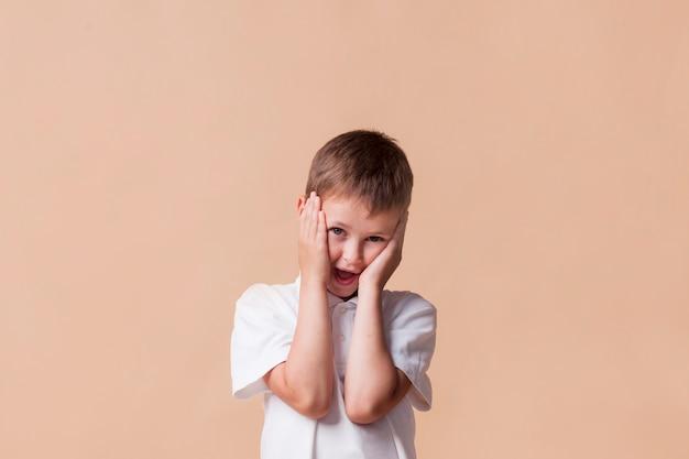 Primer plano de niño lindo sorprendido con la boca abierta de pie cerca de la pared de color beige