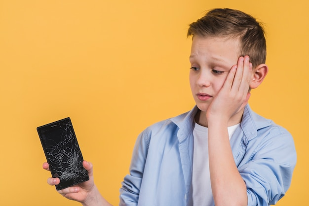 Primer plano de niño molesto mirando la pantalla rota del teléfono móvil contra el fondo amarillo