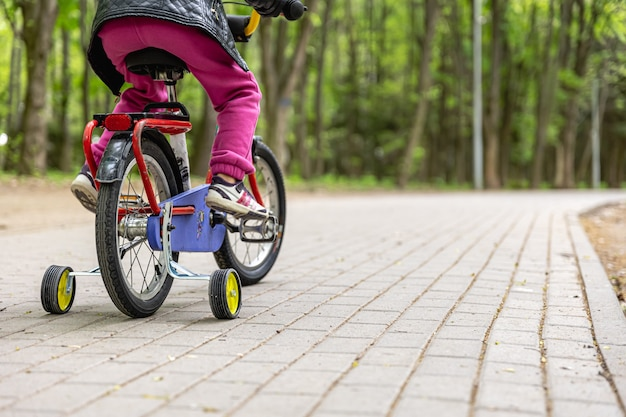 Primer plano, de, un, niño, monta una bicicleta, con, tres ruedas