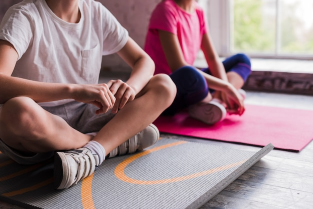 Primer plano de un niño y una niña sentados en una colchoneta de ejercicios gris y rosa