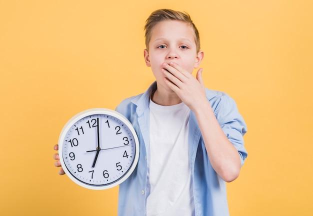 Primer plano de un niño que sostiene un reloj blanco redondo que bosteza con su mano en la boca de pie contra el fondo amarillo