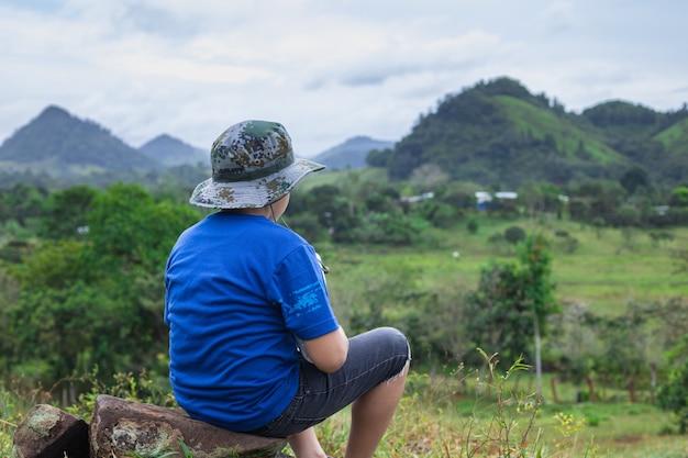 Primer plano de un niño sentado en una piedra con la vista de las colinas y montañas