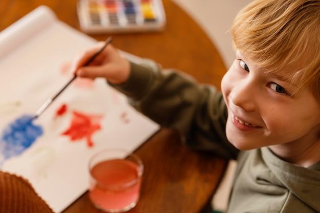 Primer plano niño sonriente pintando sobre papel
