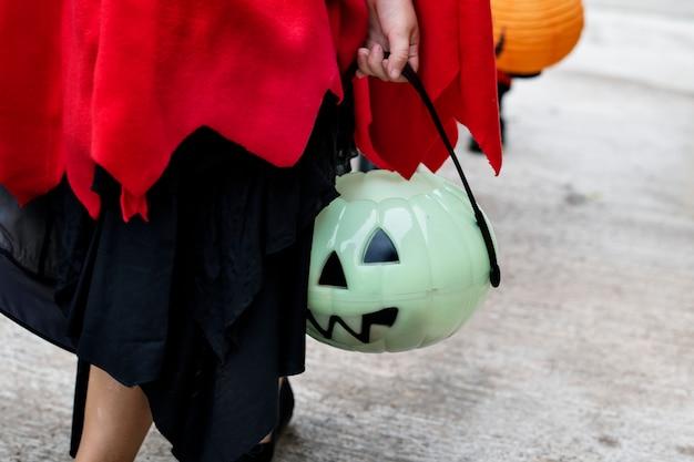 Primer plano de niño sosteniendo un cubo de halloween