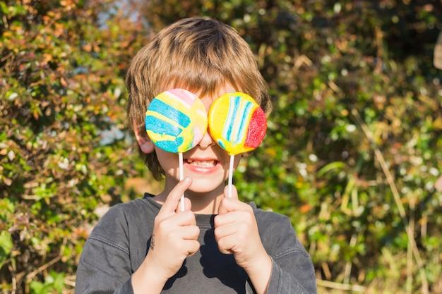 Primer plano de niño sosteniendo dos piruletas frente a sus ojos