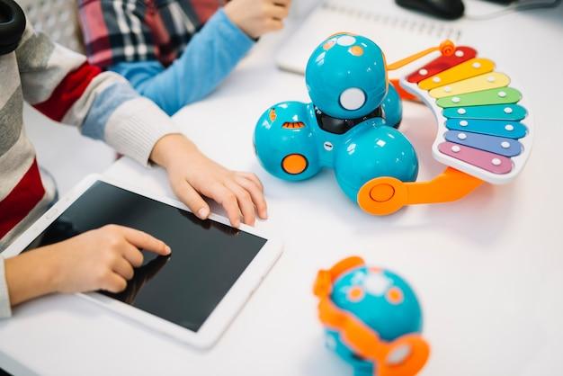 Primer plano de niño tocando la pantalla de la tableta digital en el escritorio blanco