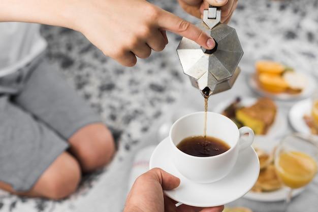 Primer plano de un niño vertiendo café negro en una taza