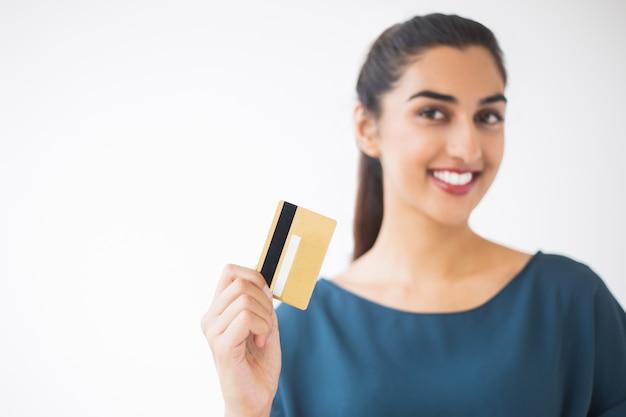 Primer plano de niza borrosa mujer que muestra la tarjeta de crédito