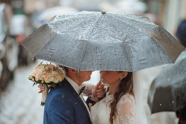 Primer plano de la novia y el novio caminando bajo el paraguas en el día de su boda