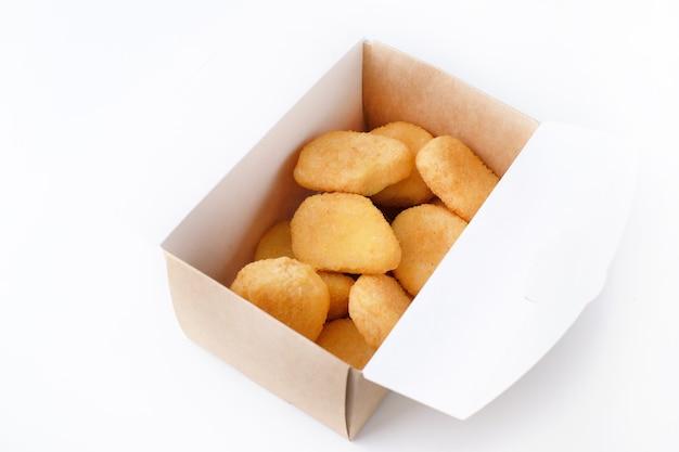 Primer plano de nuggets fritos de pollo caseros en caja de papel para entrega aislado en blanco
