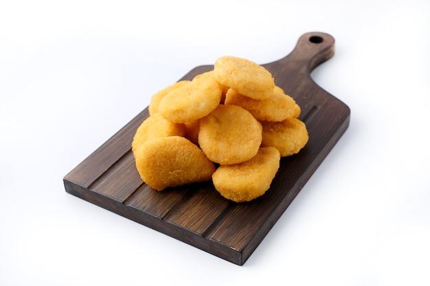 Primer plano de nuggets fritos de pollo caseros en tablero de madera aislado en blanco