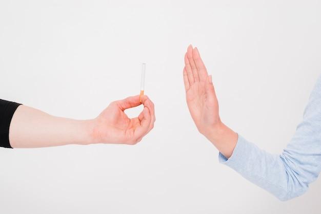 Primer plano de la oferta de cigarrillos rechazados a mano.
