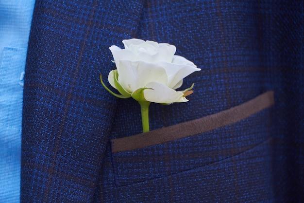 Primer plano de un ojal rosa blanco en el bolsillo de una chaqueta de traje azul