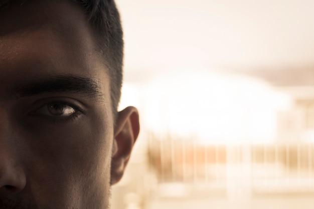 Primer plano del ojo de un joven en las sombras