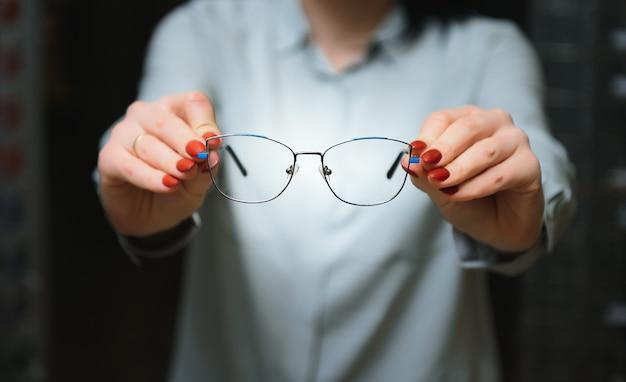 Primer plano de un optometrista, óptico dando gafas para probar