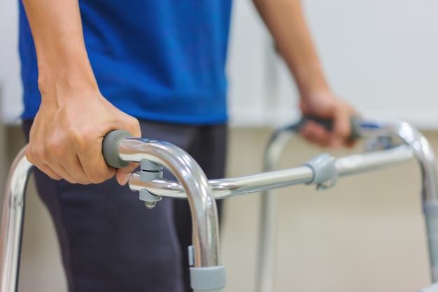 Primer plano, paciente masculino de mediana edad está utilizando caminantes para practicar caminar después de la cirugía.