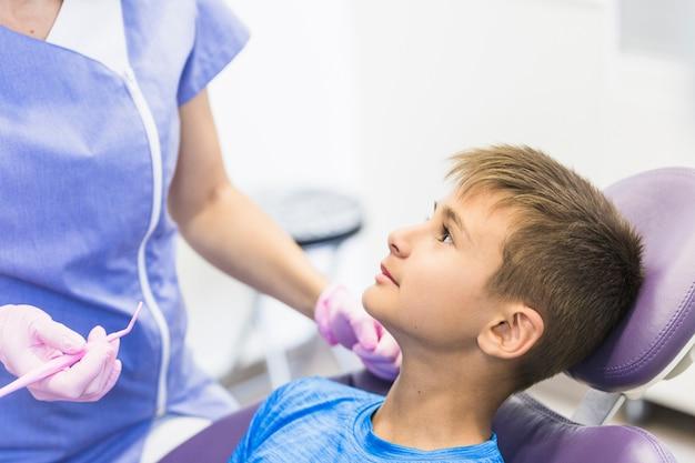 Primer plano de un paciente niño apoyado en una silla dental en clínica