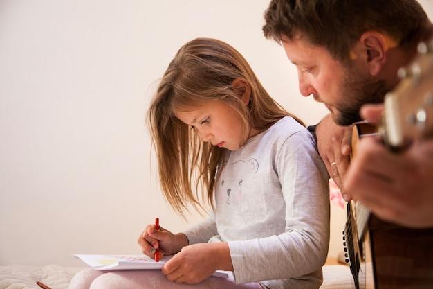 Primer plano de padre mirando a su hija dibujar