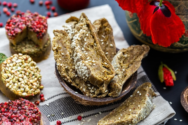 Primer plano de pan crudo vegano con amapolas sobre una mesa oscura