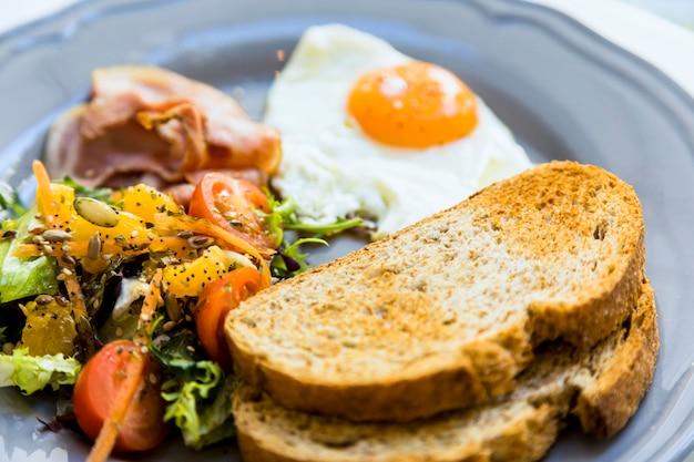 Primer plano de pan tostado; huevos fritos; ensalada y tocino servido en plato cerámico.