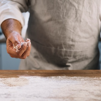 Primer plano de panadero espolvoreado en mesa de madera con harina de trigo