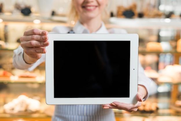 Primer plano de un panadero femenino mostrando tableta digital con pantalla en blanco
