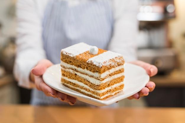 Primer plano de un panadero femenino que sirve la rebanada de los pasteles en la placa blanca de la forma del corazón