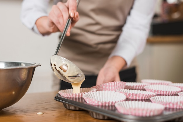 Primer plano del panadero femenino que vierte la mezcla de la torta mezclada en el soporte de la magdalena