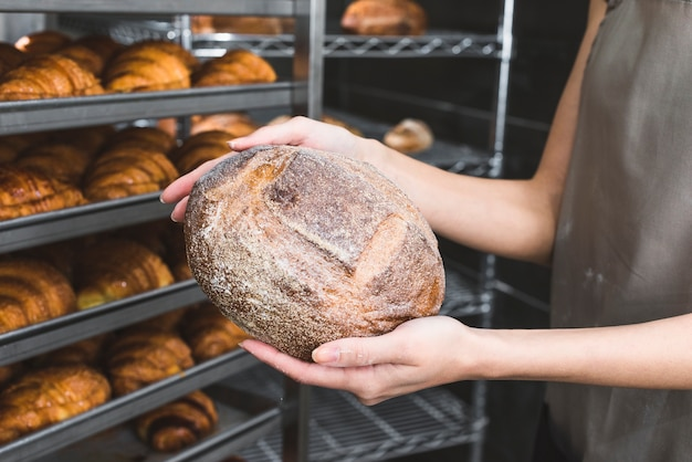 Primer plano de panadero femenino sosteniendo pan rústico en frente de estantes al horno